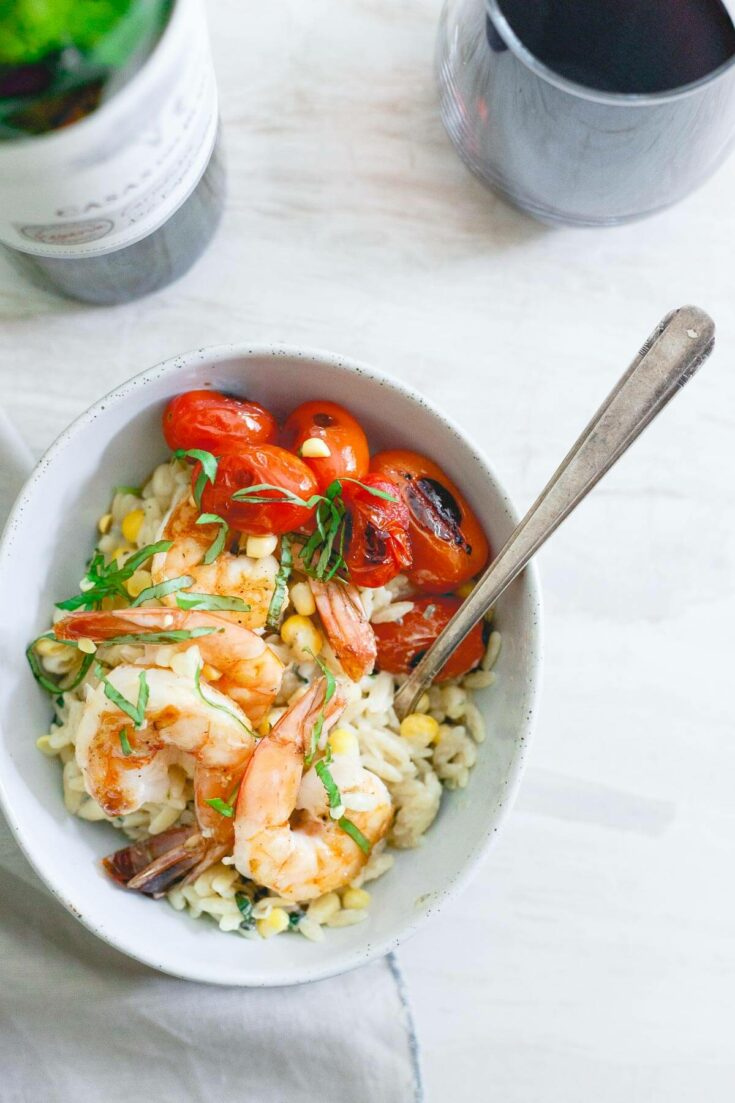 This brown butter shrimp is served on top of a creamy parmesan basil corn orzo and blistered cherry tomatoes for the perfect summer date night meal.