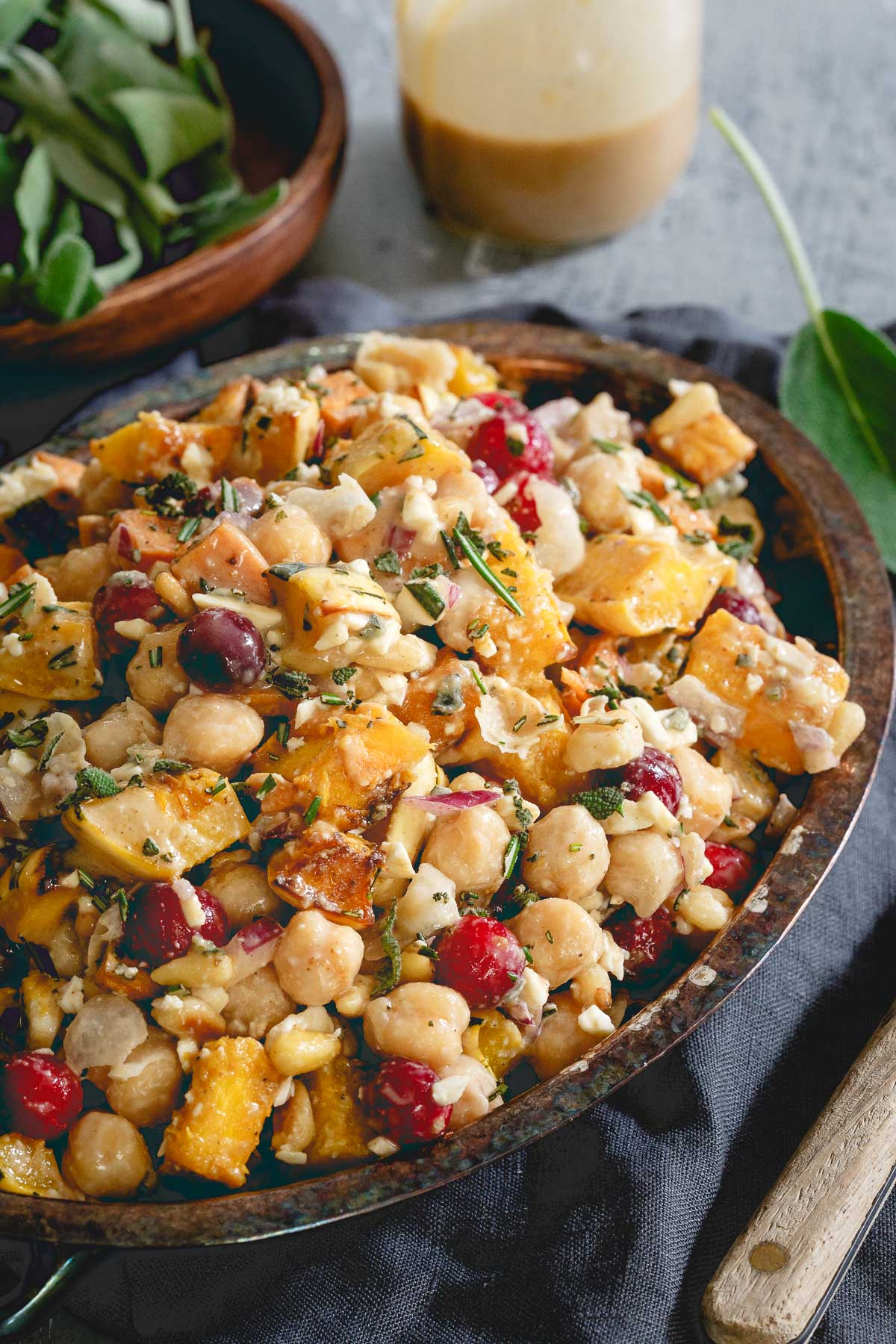 This chickpea fall salad is a hearty vegetarian meal with roasted sweet potatoes, delicata squash, cranberries, feta and a tahini maple dressing.
