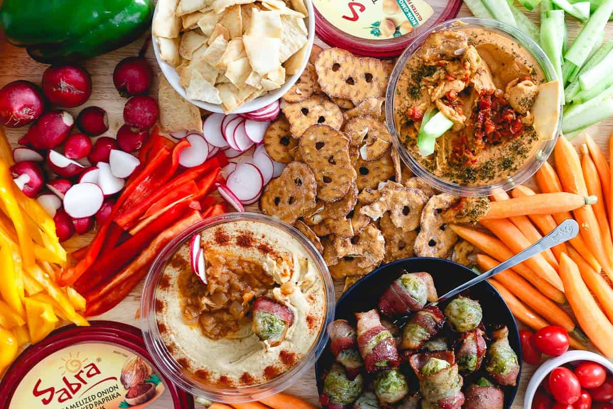 There's something for everyone in this game day spread that includes hummus, vegetables, pretzels, pita chips and bacon wrapped brussels sprouts.