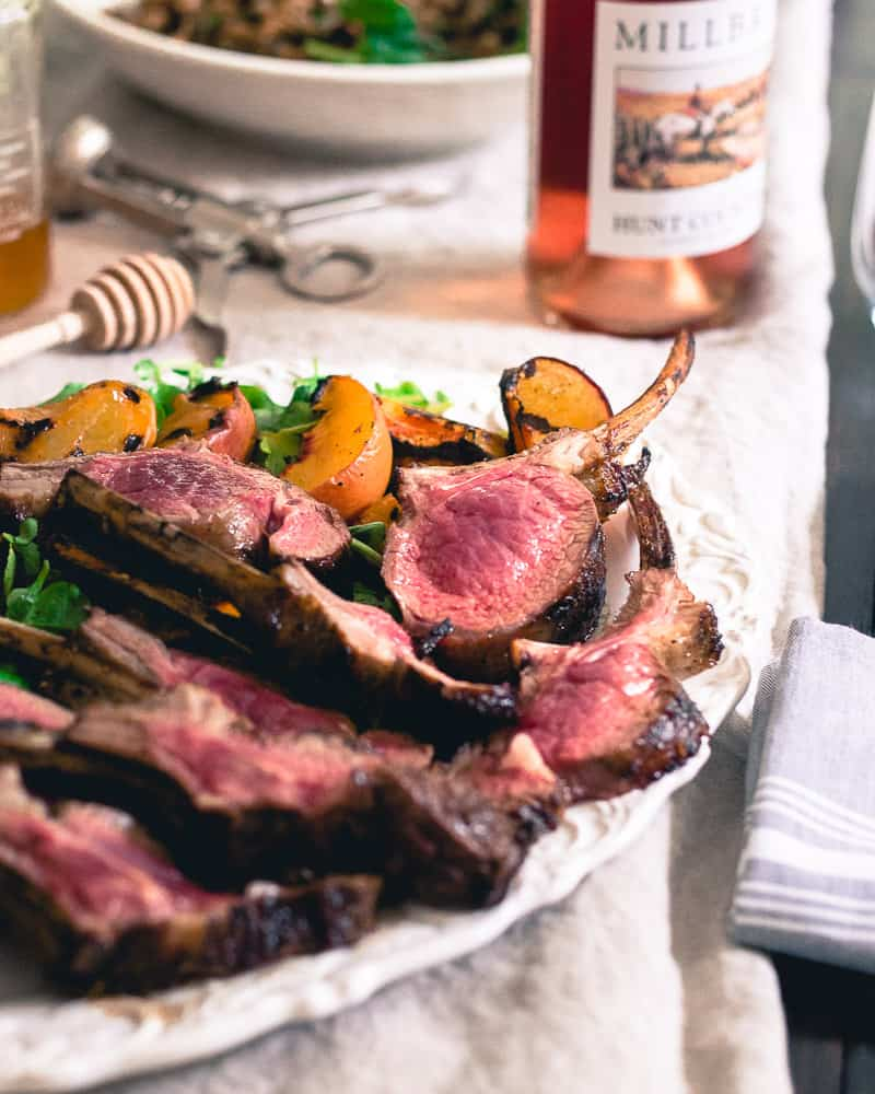 Grilled lamb chops with a sweet peach honey glaze are served with a simple watercress and peach salad for easy summer entertaining.