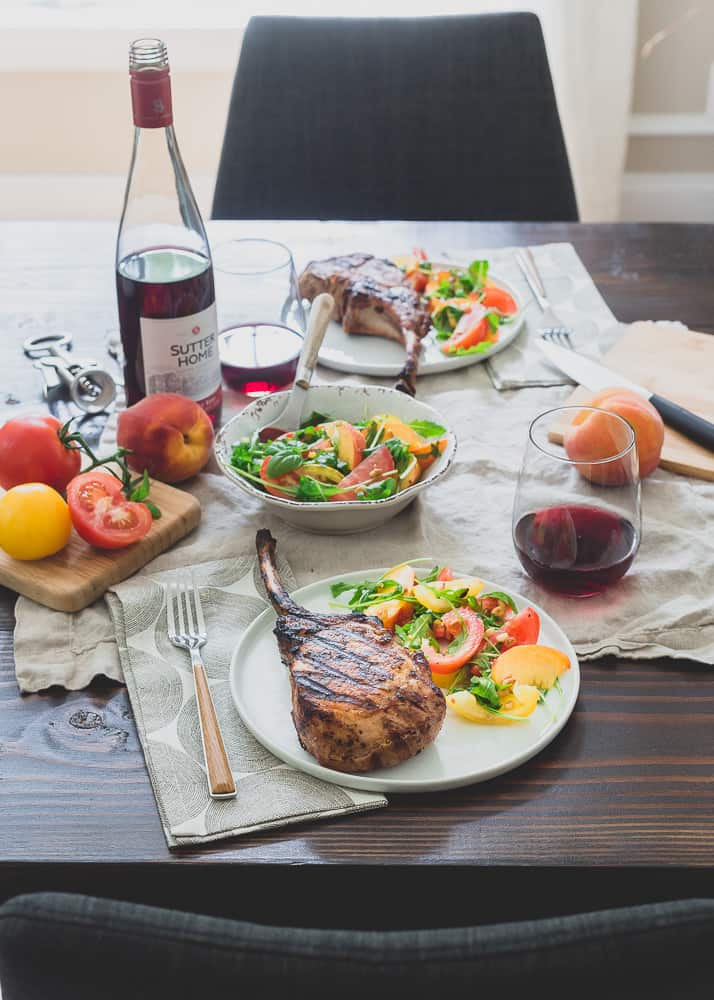 Harissa rubbed grilled pork chops are a simple, spicy summer meal perfectly paired with a ripe peach and tomato salad and glass of sweet red wine.