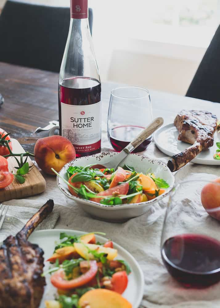 Sutter Home Sweet Red wine goes perfectly with these harissa rubbed grilled pork chops and tomato peach salad.