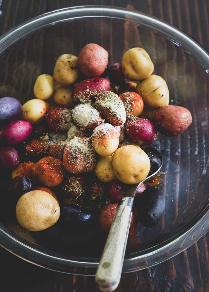 Small red, white and purple potatoes with peri peri spice before being roasted.