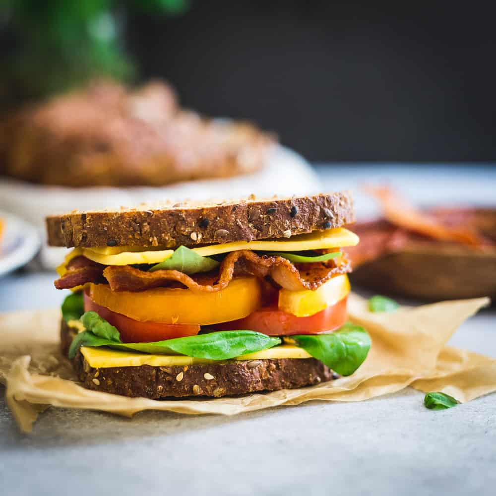 This BLTC sandwich draws inspiration from all the delicious late summer produce using heirloom tomatoes and fresh basil for a seasonal twist to the classic on seedy multigrain bread.