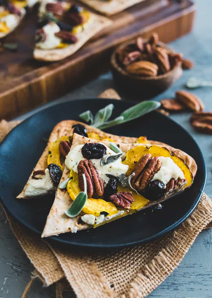 This winter inspired delicata squash flatbread is topped with pecans, dried cherries and dollops of ricotta. Fresh sage makes it a great for a holiday appetizer.