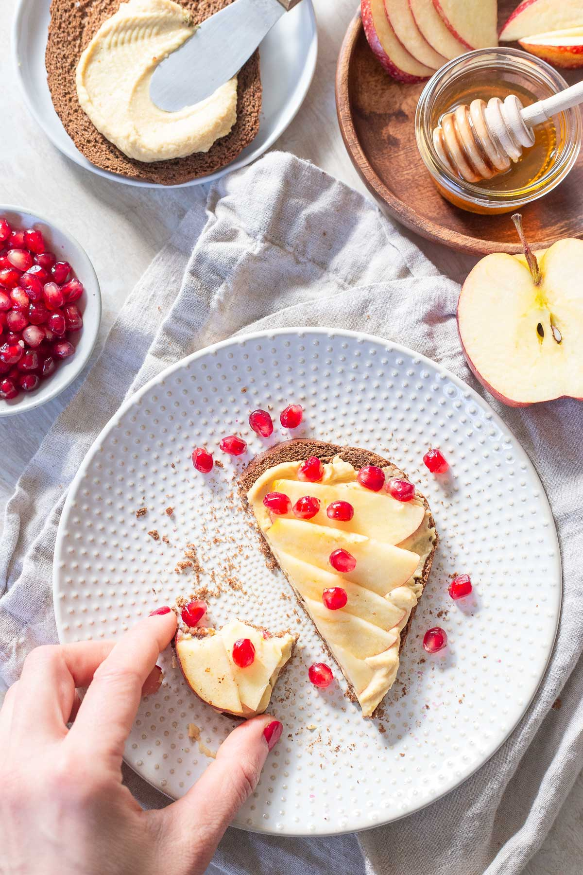 Quick and easy hummus toast with apple slices and fresh pomegranates is the perfect snack for winter.