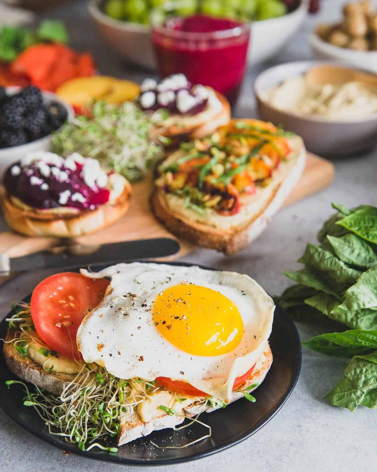 Hummus sourdough toast with sprouts, tomato and a fried egg is the perfect savory bite with this easy beet smoothie.