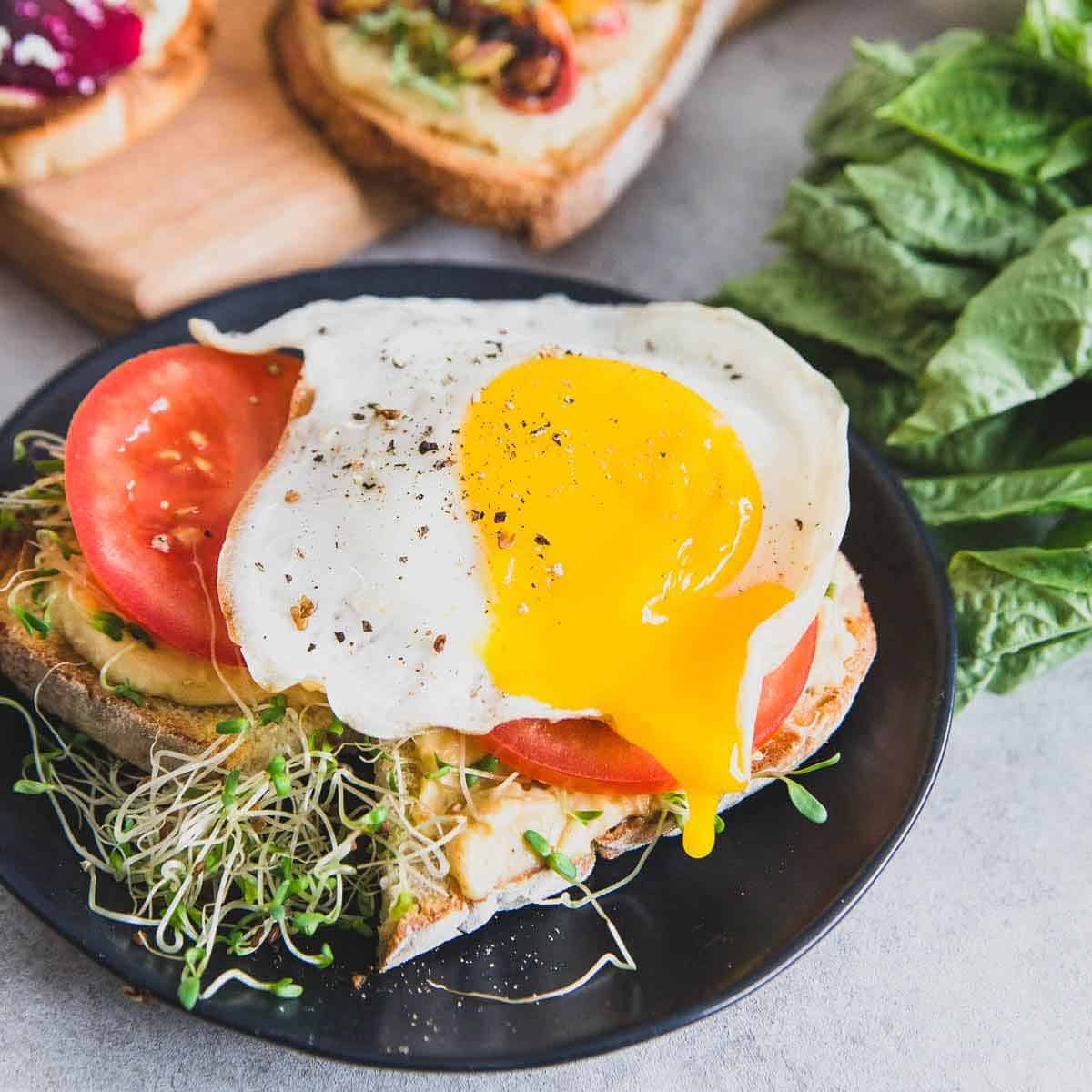 A runny fried egg tops sourdough hummus toast with fresh tomato slices along with a delicious beet smoothie recipe.