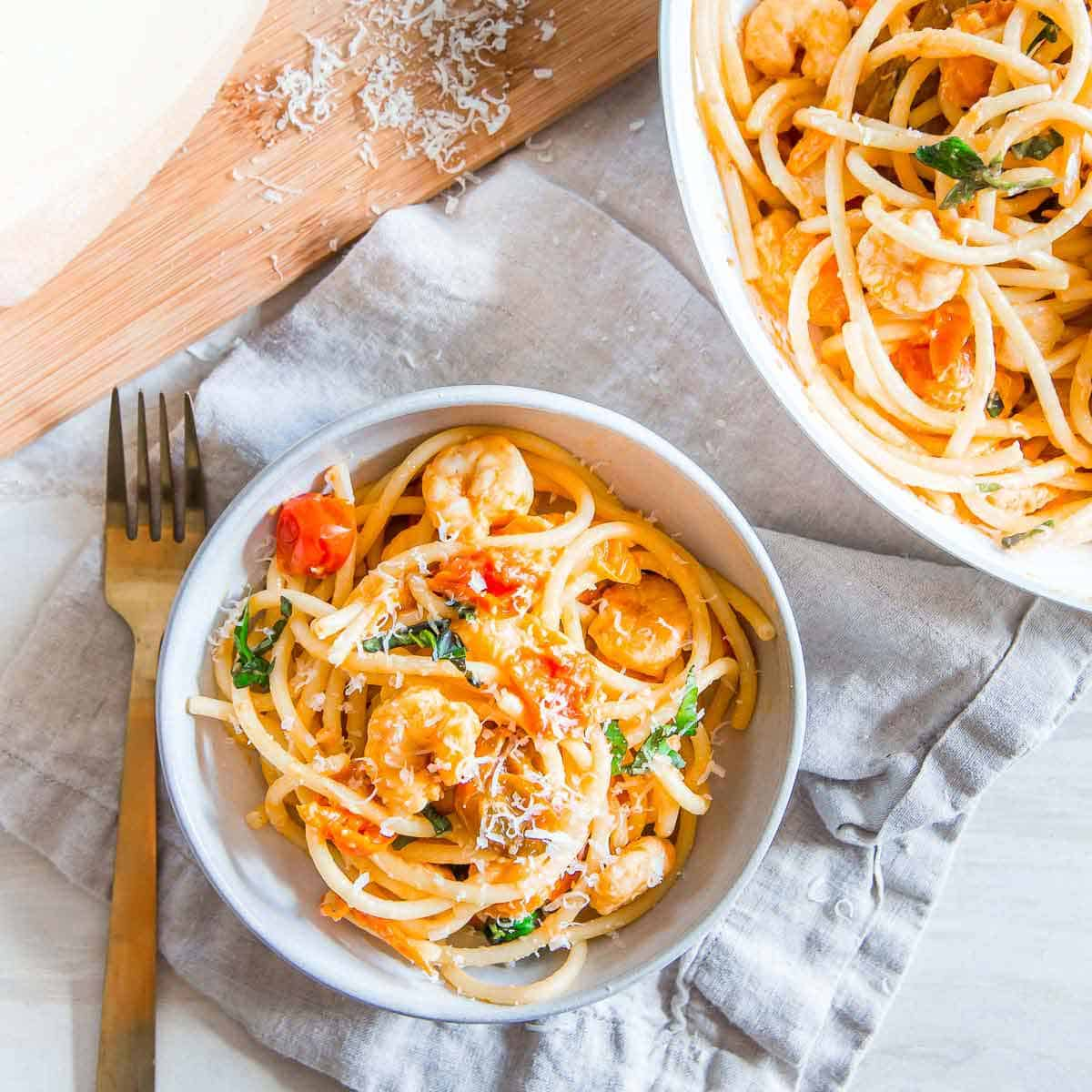 This easy bucatini pasta recipe tossed with garlic shrimp and cherry tomatoes is made in under 30 minutes making it a great weeknight meal.