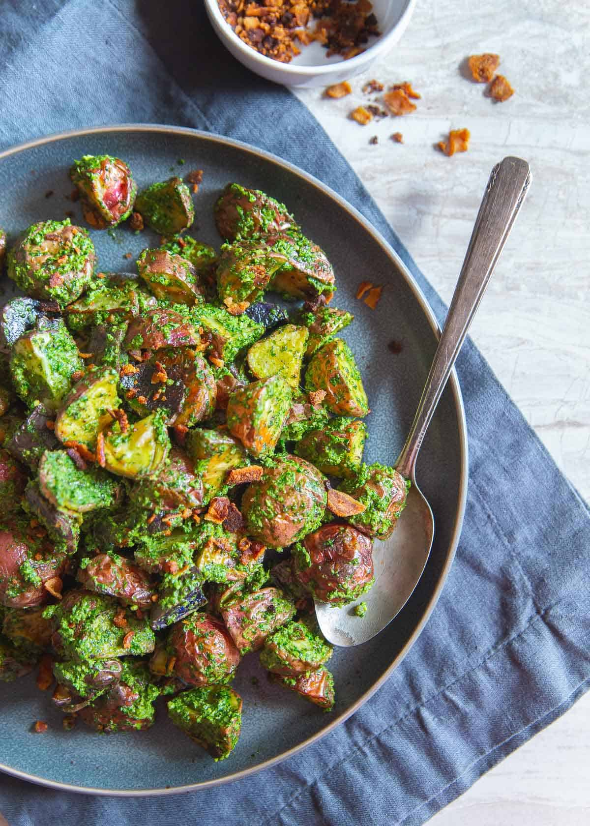 These easy roasted pesto potatoes with optional crumbled bacon make the best easy side dish that goes perfectly with any meat or fish dinner.