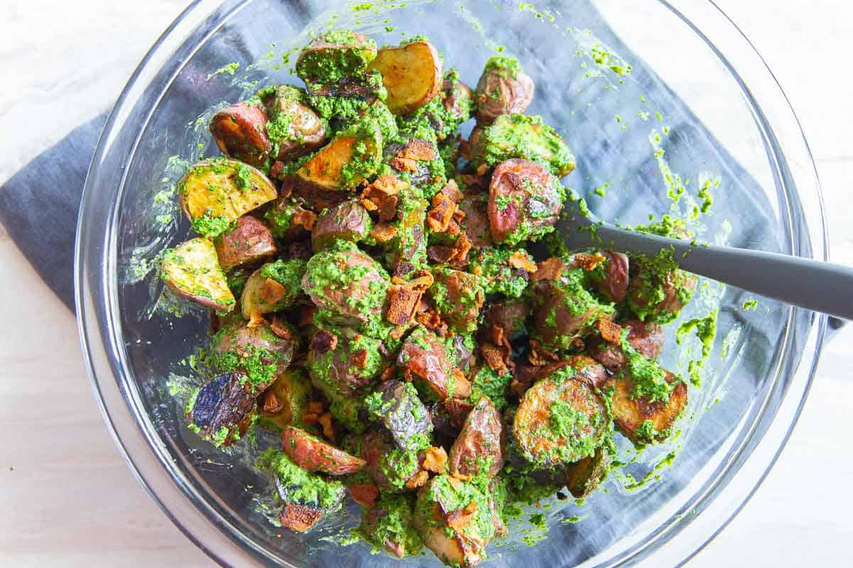 Toss roasted potatoes with fresh pesto and crispy bacon for a delicious and easy side dish.