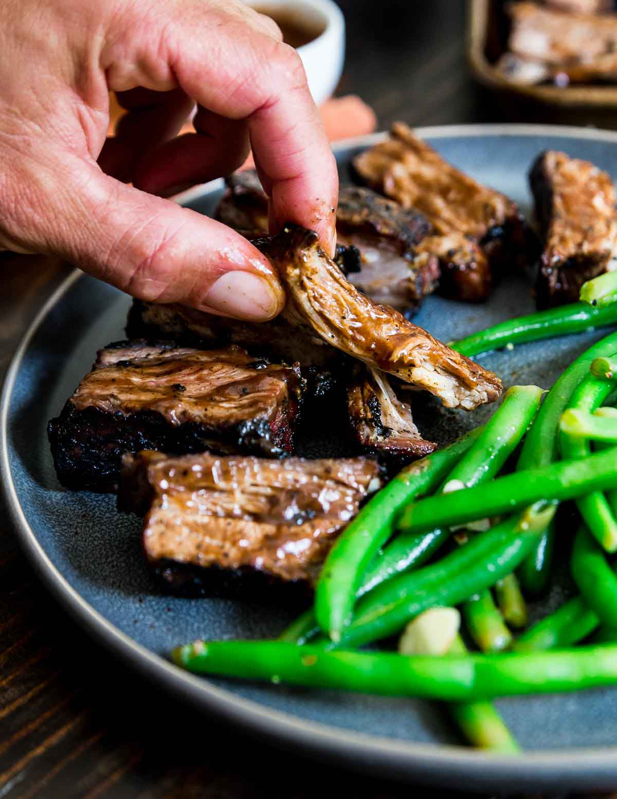 Slathered in BBQ spices and sauce, these grilled lamb riblets are a delicious summer meal.