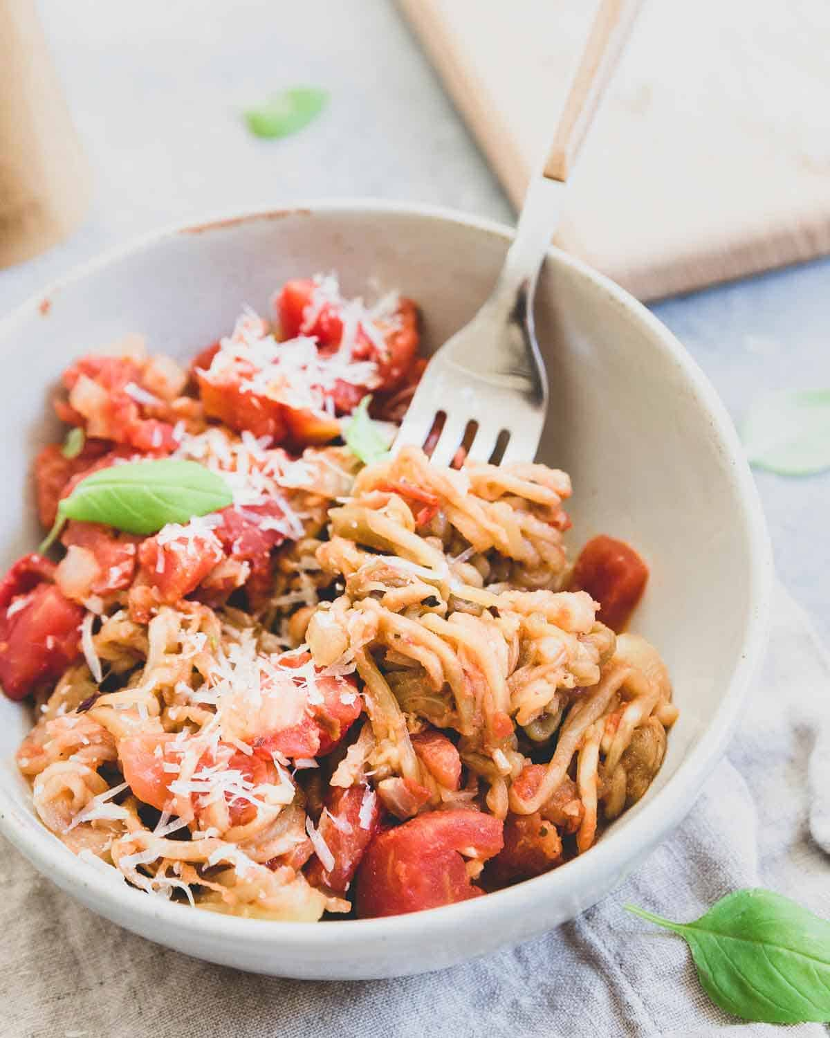 This simple eggplant noodle recipe is tossed with a quick tomato basil sauce and lots of parmesan cheese for a fresh summer meatless meal.