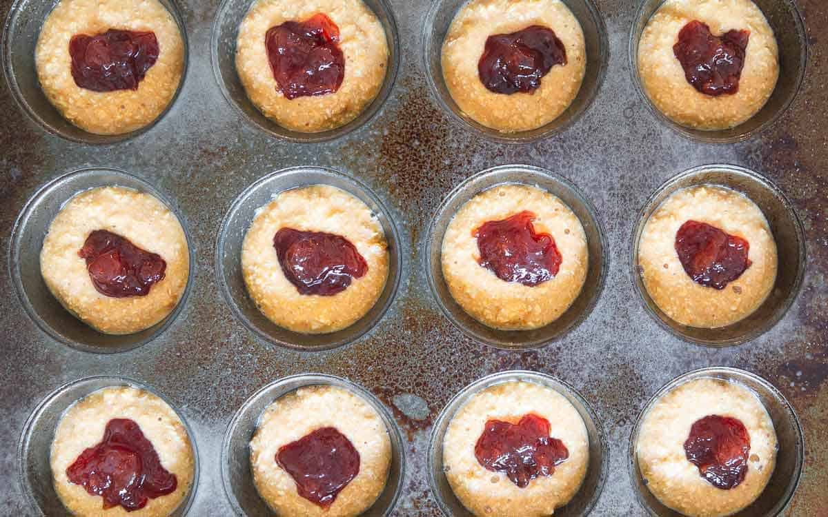 Dollops of strawberry jelly hide inside the center of each peanut butter muffin