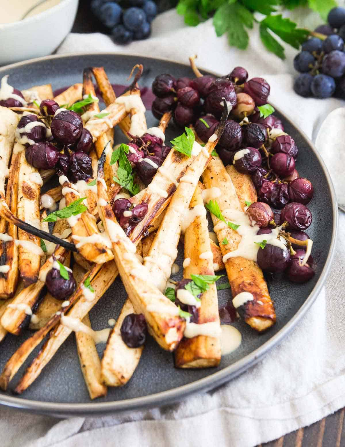 Roasting parsnips and concord grapes with cinnamon and brown sugar totally transform this side dish into something special and unique. Try it for your holiday dinner!