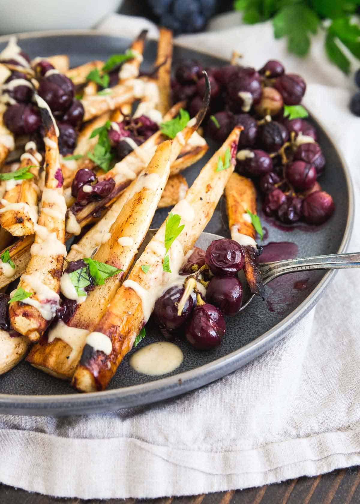 These sweet roasted parsnips and grapes make a show stopping side dish for any winter holiday meal.