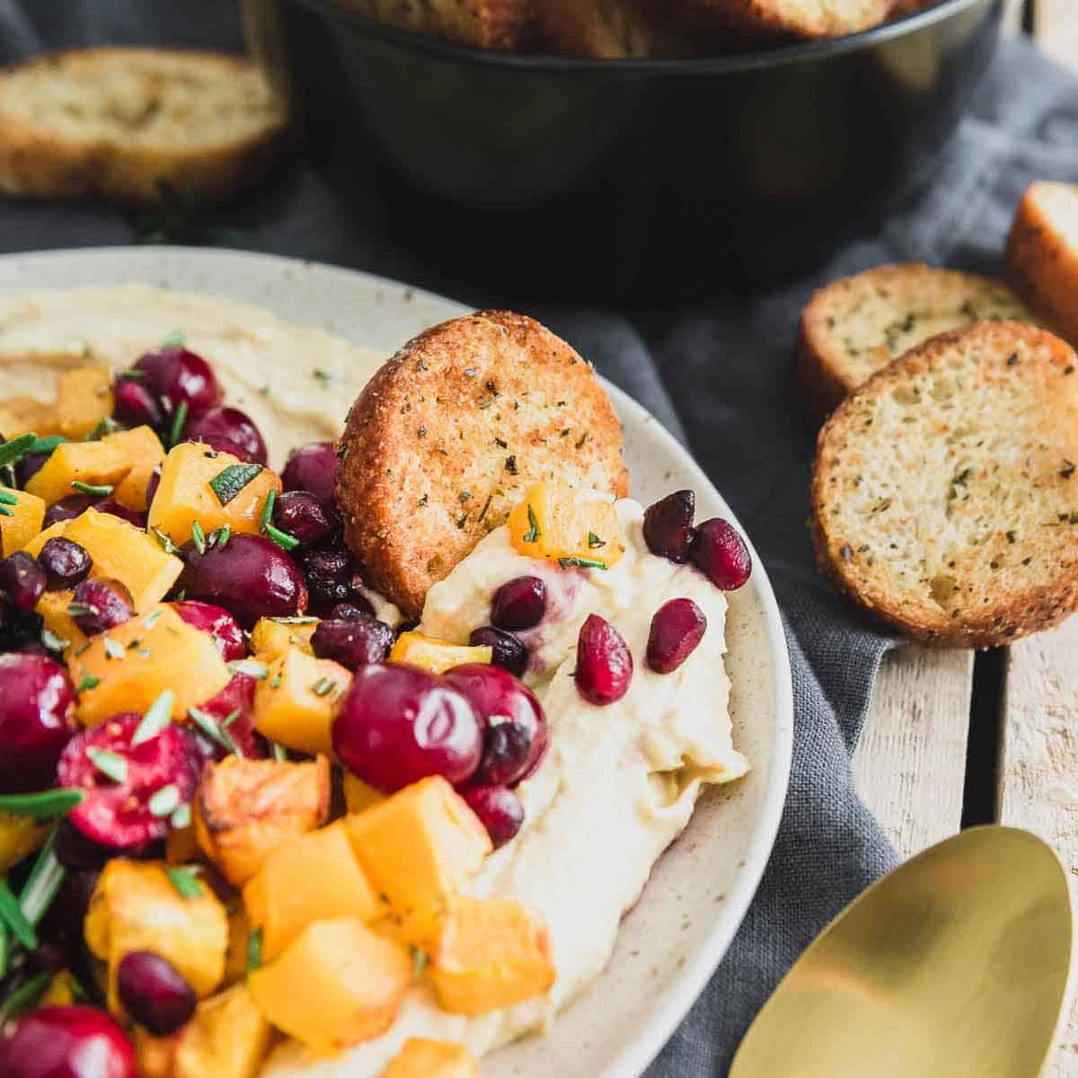 Impress your guests this season with holiday hummus featuring butternut squash, cranberries and pomegranates.