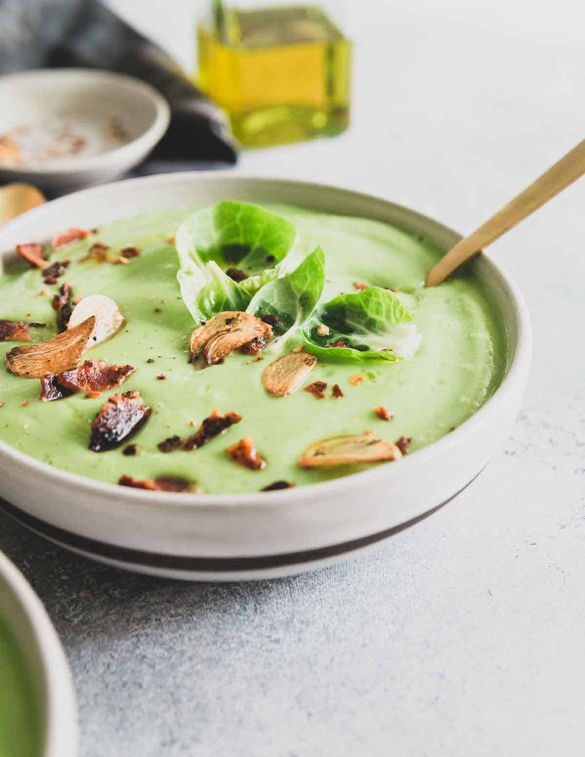 A creamy Brussels sprout soup packed with lots of garlic flavor and garnished with crispy bacon and fried garlic chips.