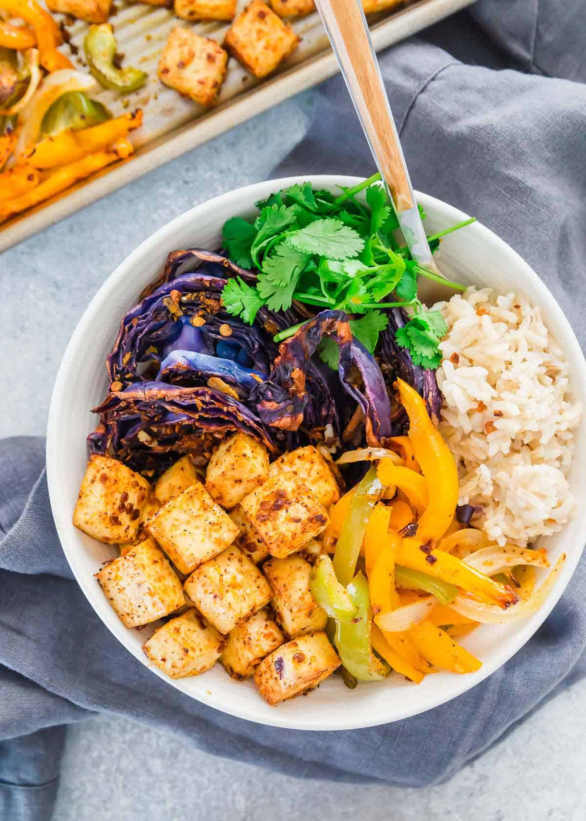 Crispy roasted tofu meal prep with cabbage, peppers, onions and brown rice made on a sheet pan is easy and nutritious.