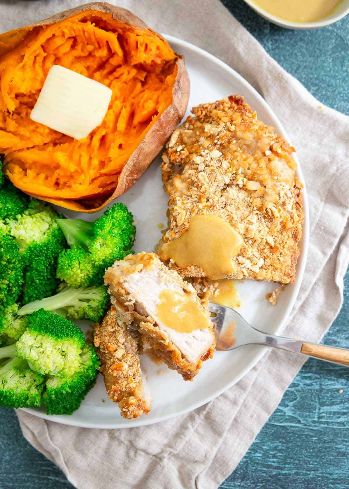 Pretzel pork chops baked in the oven with broccoli and sweet potato make a nutritious and delicious weeknight dinner.