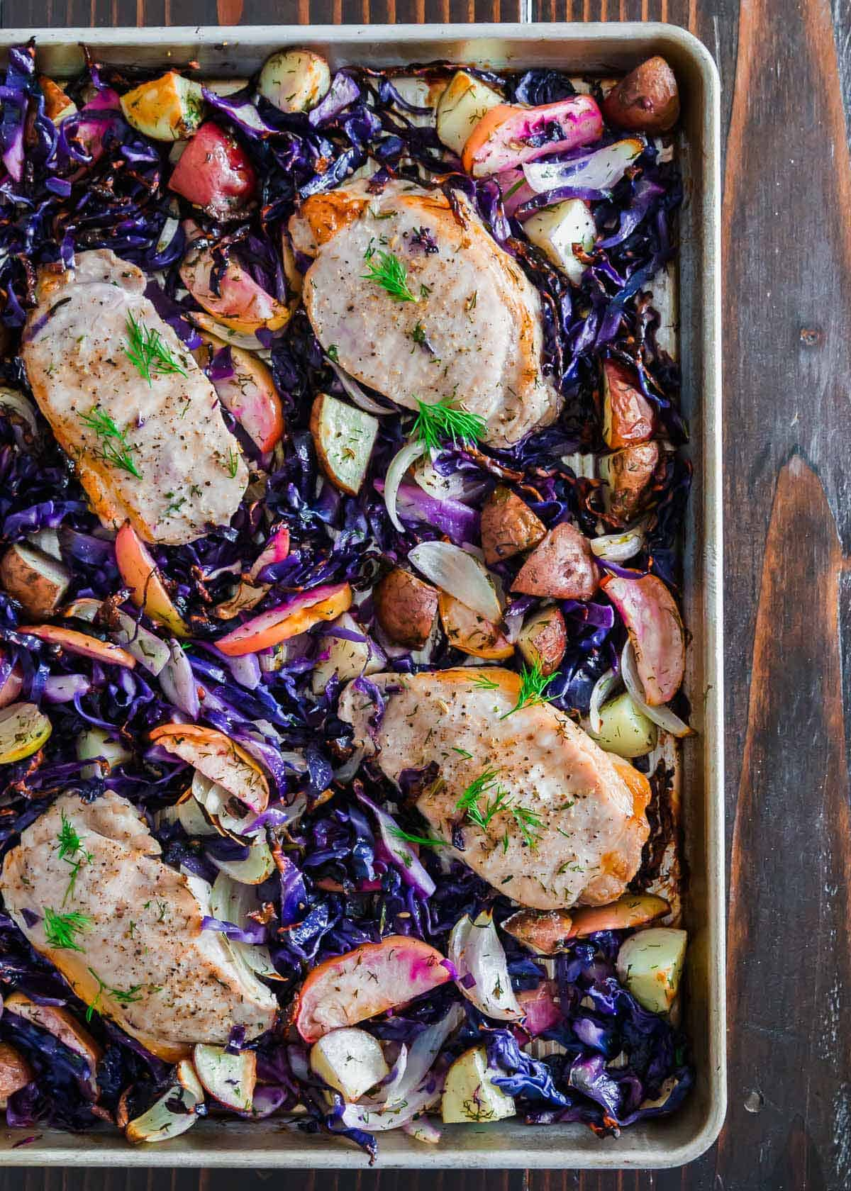 Roasted to perfection, these boneless pork chops with apples, potatoes and cabbage make a quick and easy weeknight sheet pan meal.
