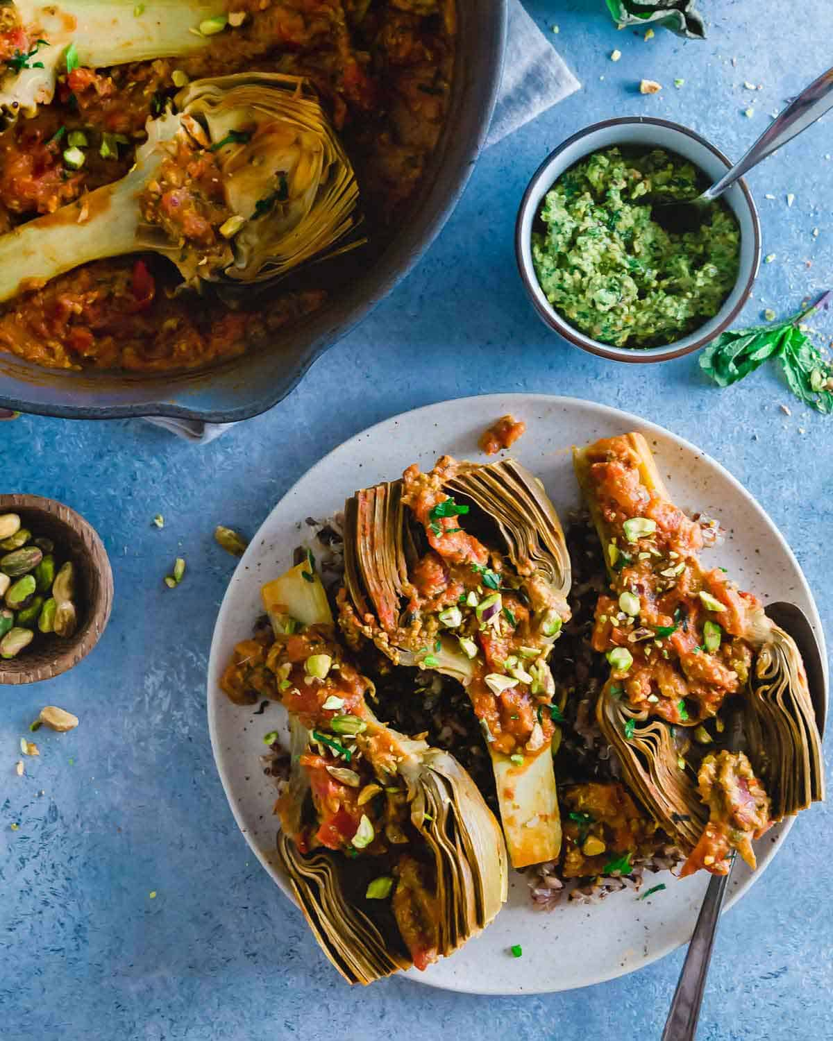 Braised artichokes cooked with tomatoes until fork tender and served with pistachio pesto are an absolutely delicious vegetarian side dish.
