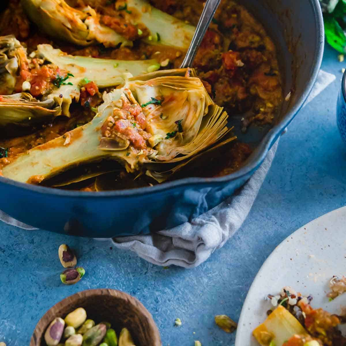 Once you braise artichokes, you'll never want to cook them another way again. Perfectly tender, full of flavor from reduced tomatoes, white wine and a deliciously nutty pistachio pesto.