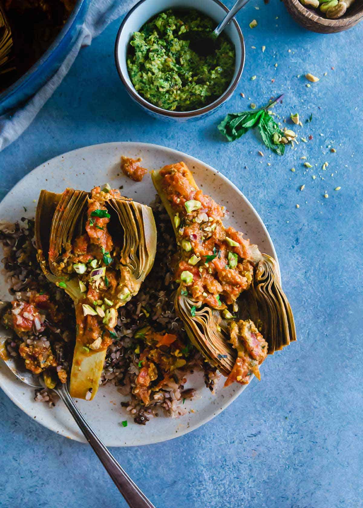 An easy recipe for braised artichokes with a chunky white wine tomato sauce and a bright pistachio pesto.