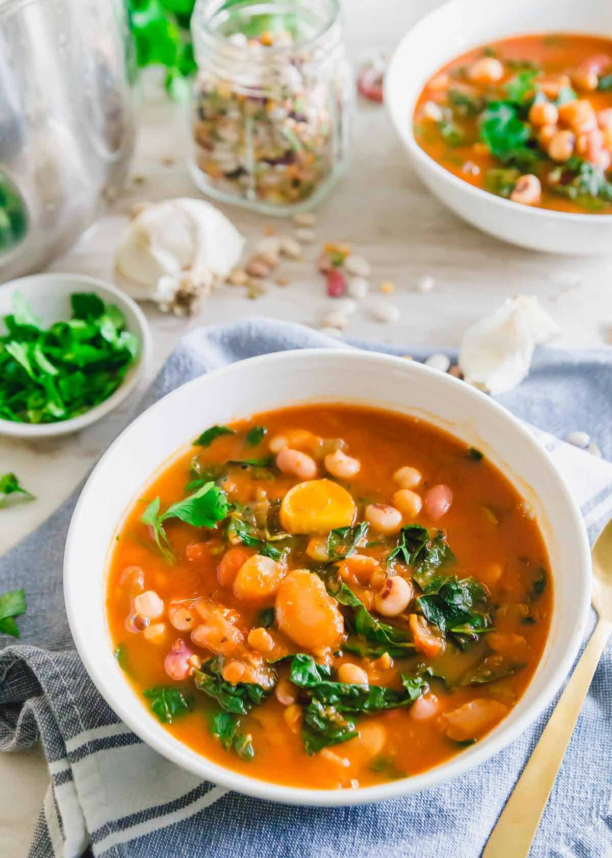This Instant Pot bean soup recipe uses a 13 bean and lentil blend with a hearty tomato base for a cozy vegan meal. Tuscan kale leaves are stirred in at the end for added color and nutrition.