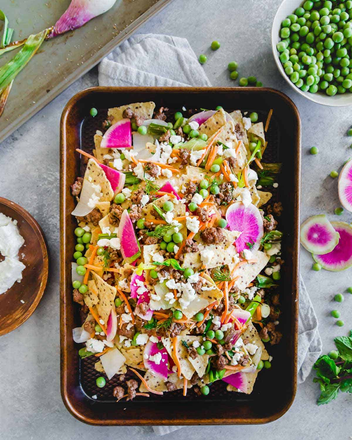 These ground American lamb nachos with carrots, onions, peas and radishes are topped with crumbled feta cheese for a bright and fresh spring take on nachos. Enjoy them straight off the baking sheet for an easy seasonal dinner or appetizer.