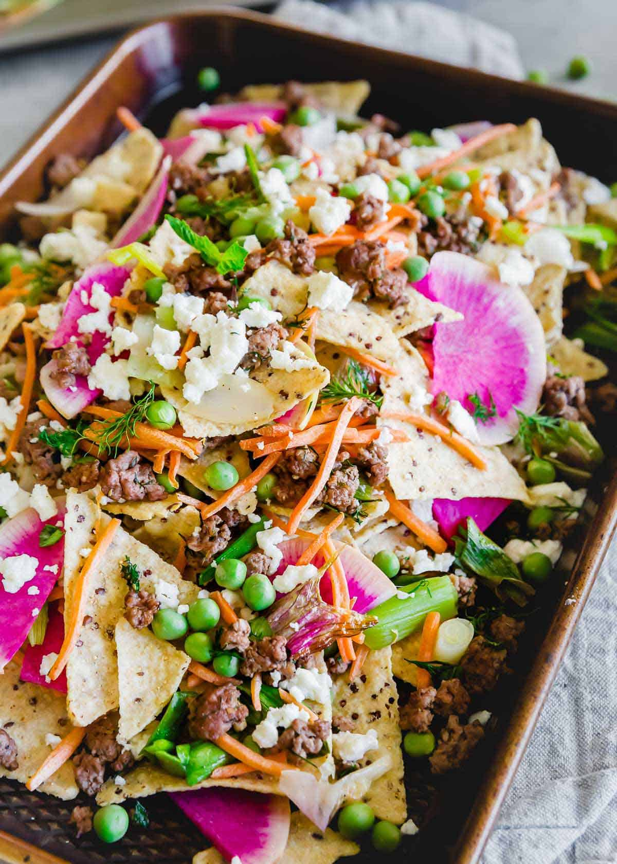Bright, colorful and full of flavor, spring lamb nachos have radishes, carrots, onions and peas piled high on corn tortilla chips with lots of feta cheese.