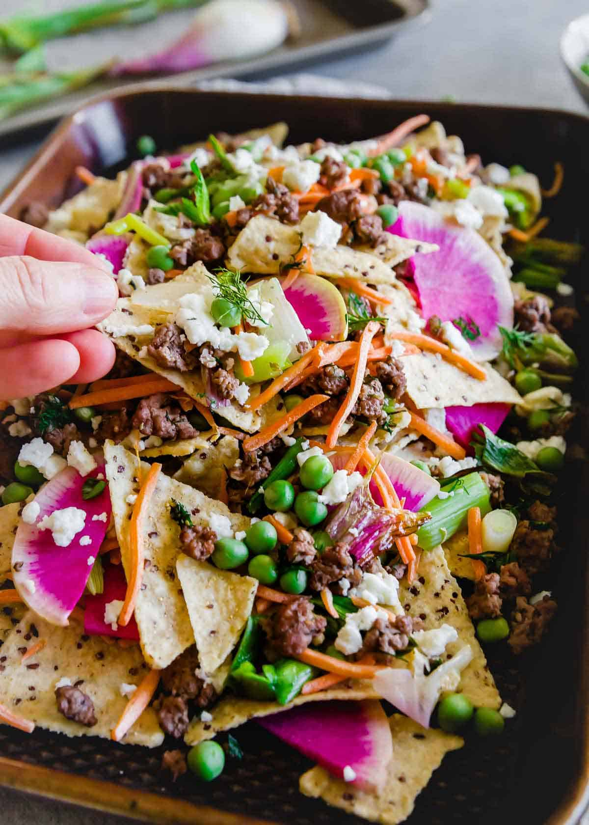 A fun spring spin on traditional nachos, these nachos use ground lamb seasoned with dill and oregano and lots of fresh spring vegetables.