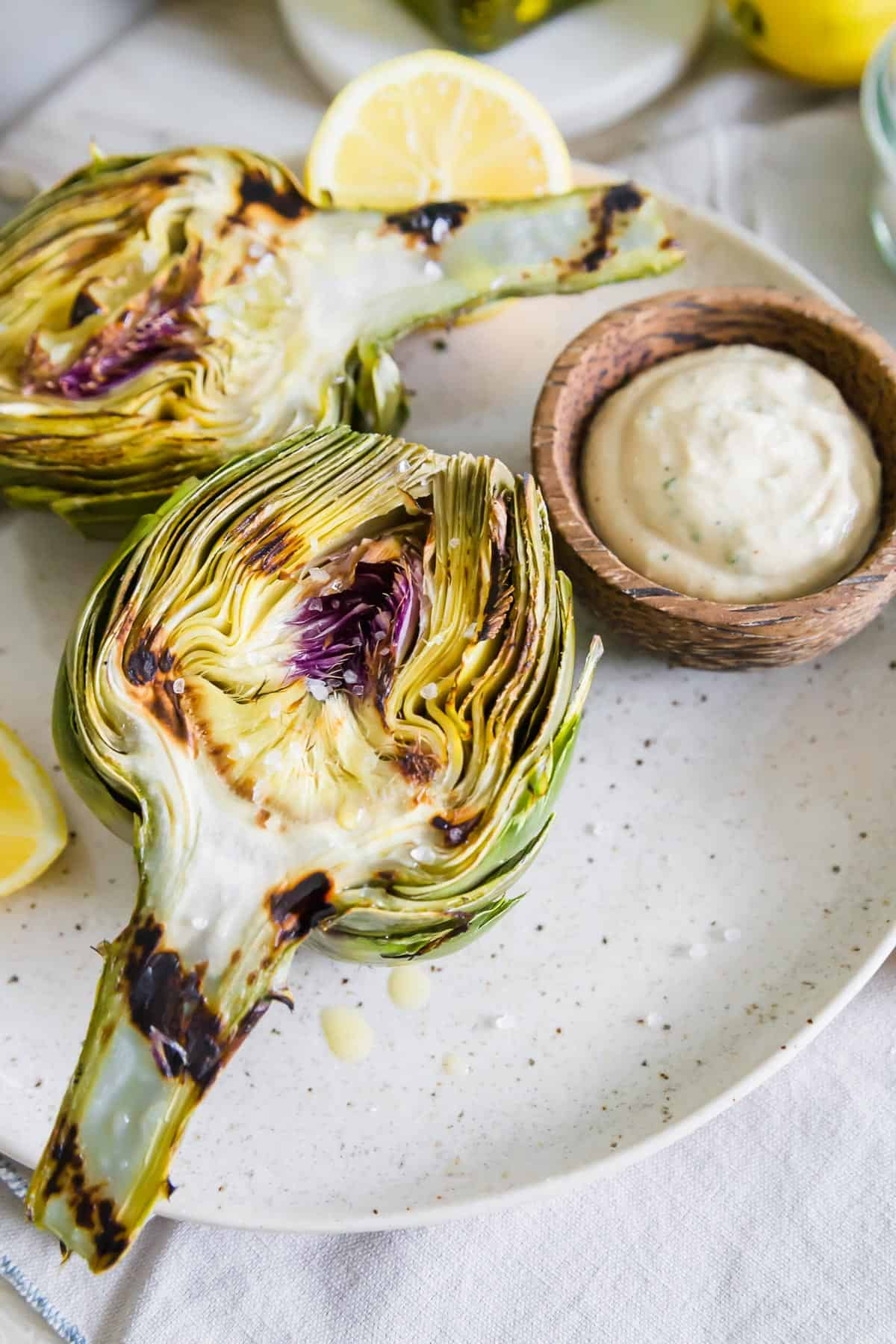 Enjoy these easy grilled artichokes with a drizzle of olive oil, sea salt and bright tahini lemon herb dipping sauce.