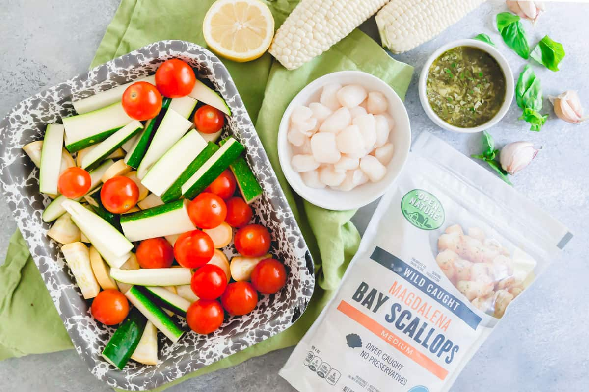 Frozen bay scallops are tossed in a garlic basil butter sauce and grilled with summer vegetables for an easy meal.