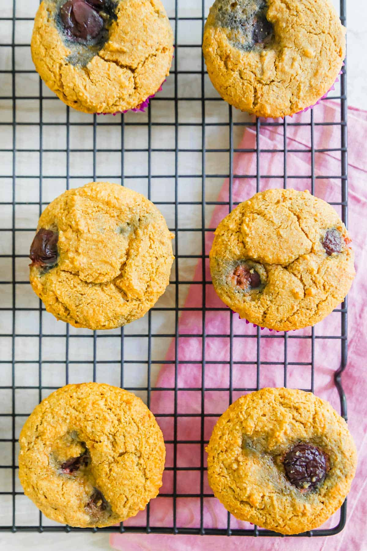 Vegan cornmeal muffins made with cornmeal and almond flour have a hearty texture and slightly sweet flavor filled with fresh summer cherries.