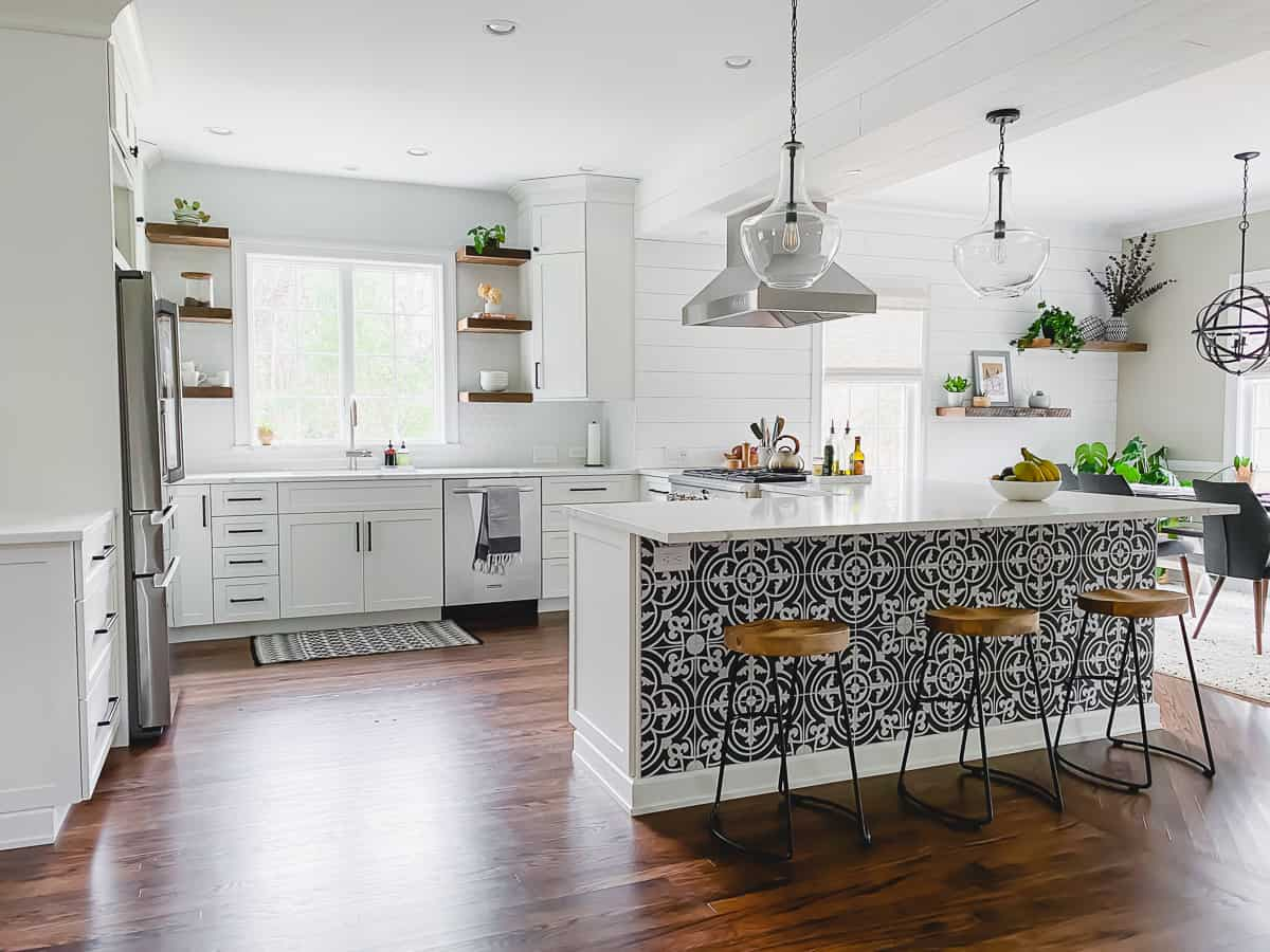This white kitchen remodel went from dark cherry cabinets and a closed off space to an open, bright space with white cabinets and reclaimed wood shelving.