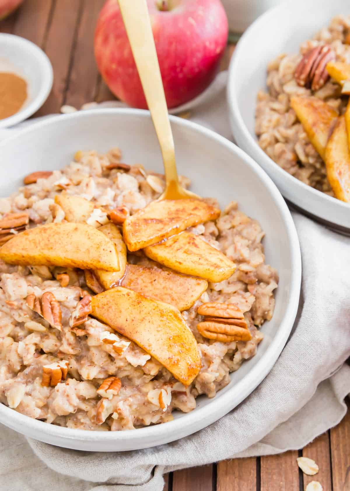 Easy stovetop apple cinnamon oatmeal with chopped pecans and maple syrup cooked apple slices.