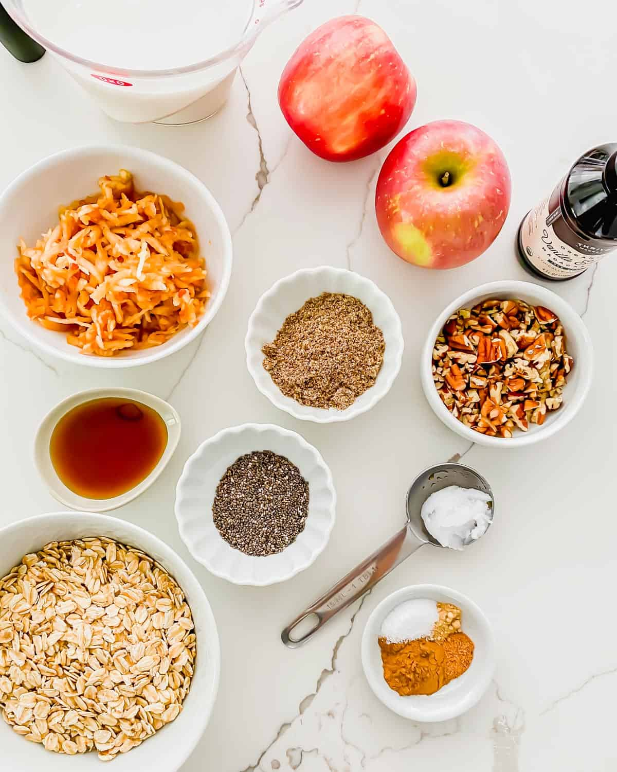 Ingredients to make apple cinnamon oatmeal: rolled oats, chia seeds, ground flaxseed, cinnamon spices, chopped pecans, grated apple, vanilla extract, maple syrup and coconut oil.