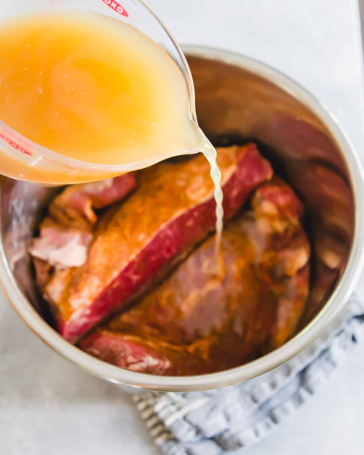 Beef broth is used as the cooking liquid for Instant Pot brisket.