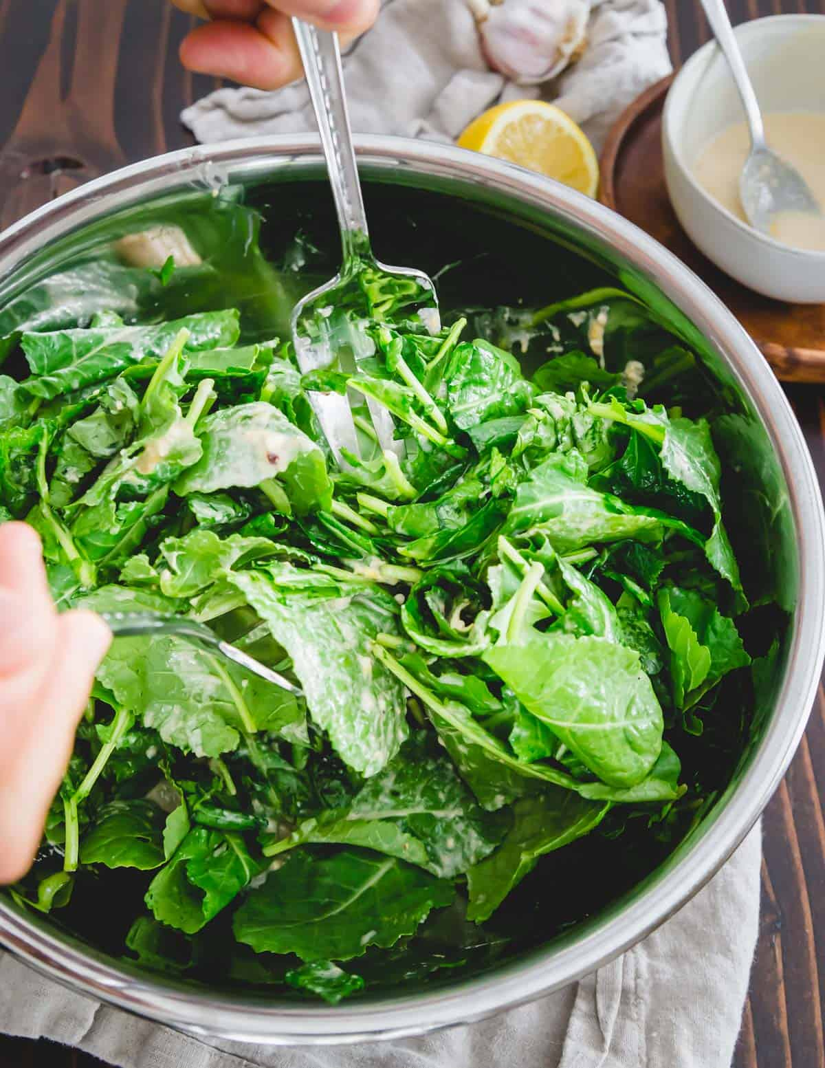 Baby kale greens are tossed in a lemon, garlic tahini dressing with nutritional yeast.