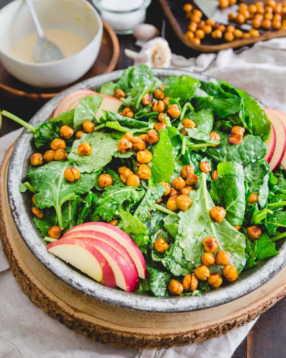 A satisfying and nutritious plant-based baby kale salad with roasted chickpeas, apples and a creamy tahini dressing.