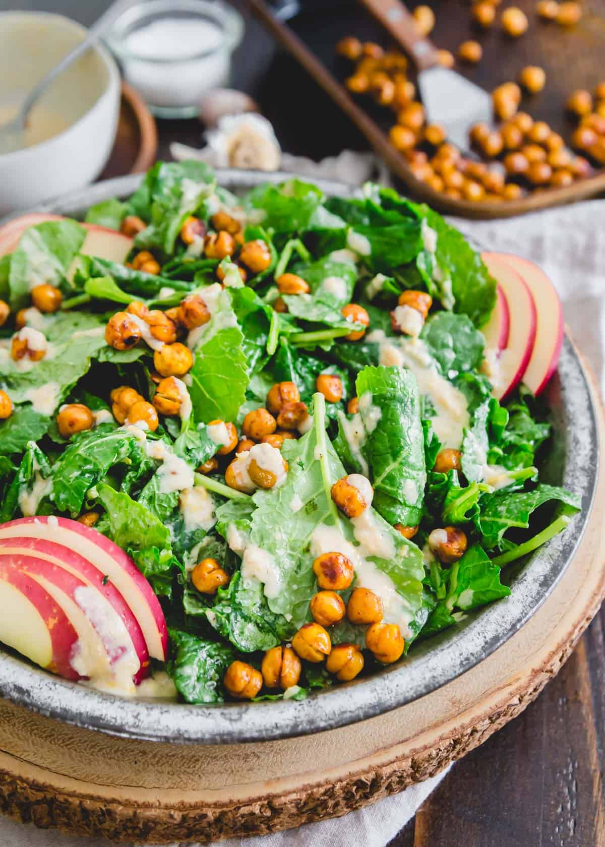 The best tasting recipe for a quick and easy baby kale salad! Tossed in a simple tahini dressing and topped with roasted BBQ chickpeas and apple slices, it's a complete plant-based meal with little effort.