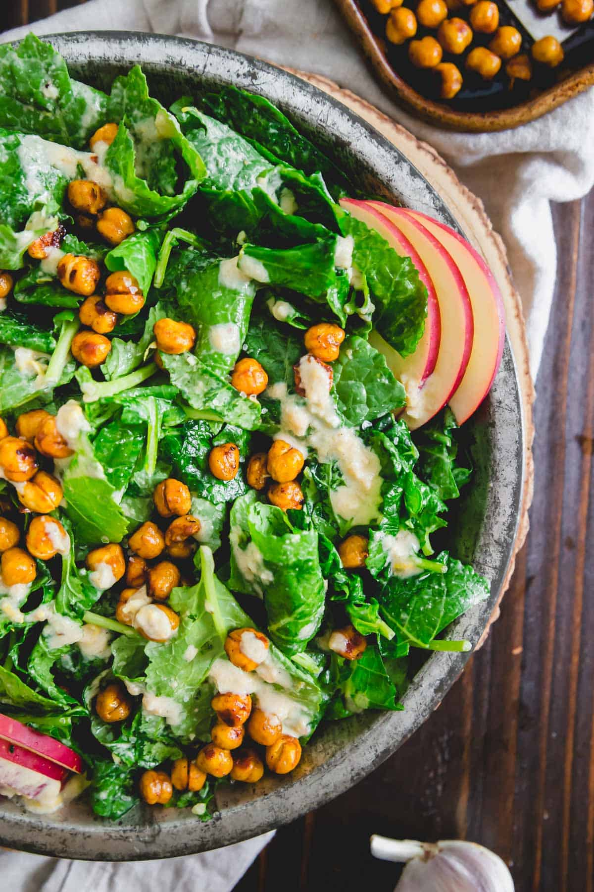 Thinly sliced apples, roasted chickpeas and a creamy tahini dressing make this the best baby kale salad recipe.