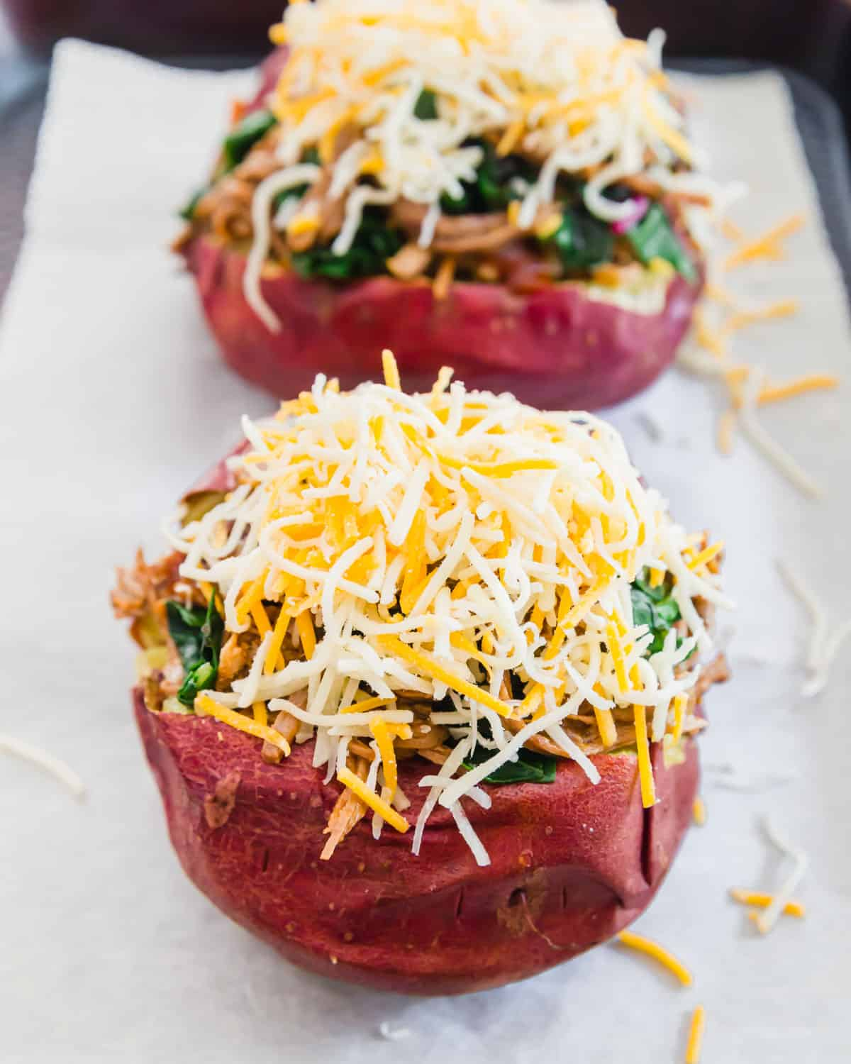 brisket stuffed potatoes before baking topped with lots of shredded cheddar cheese