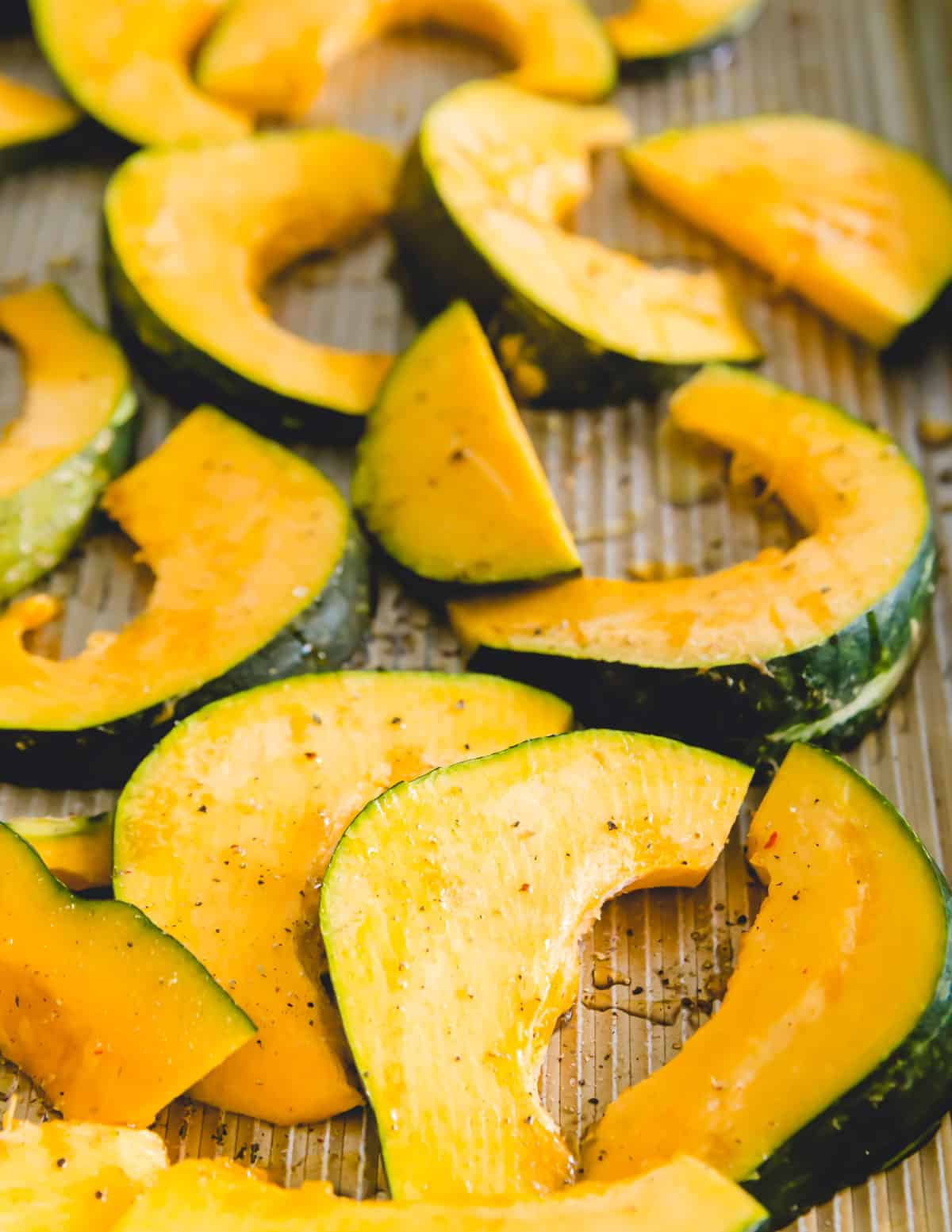 Sliced buttercup squash on a baking sheet before roasting in the oven.