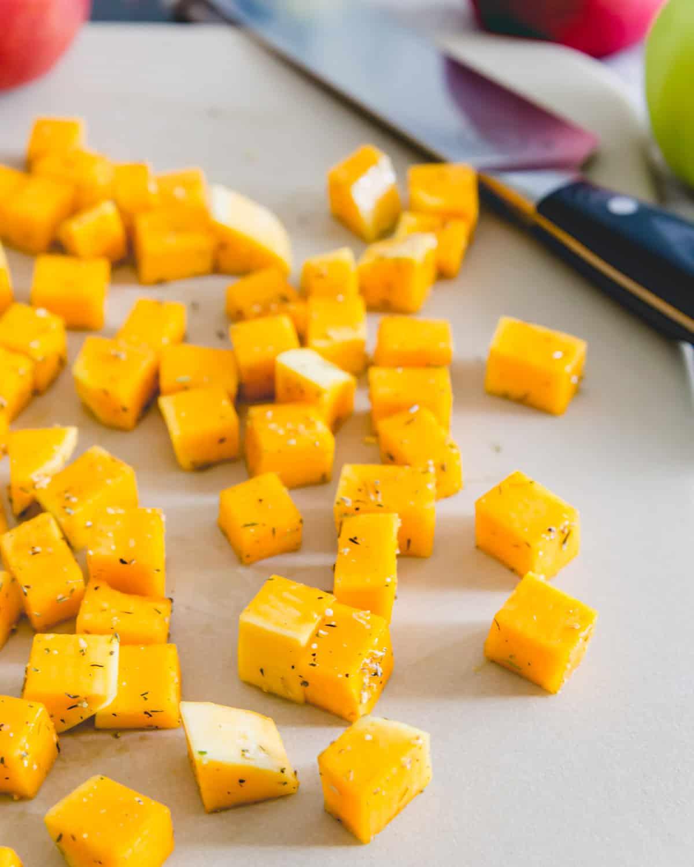 rosemary seasoned butternut squash cubes on a stoneware roasting sheet before baking