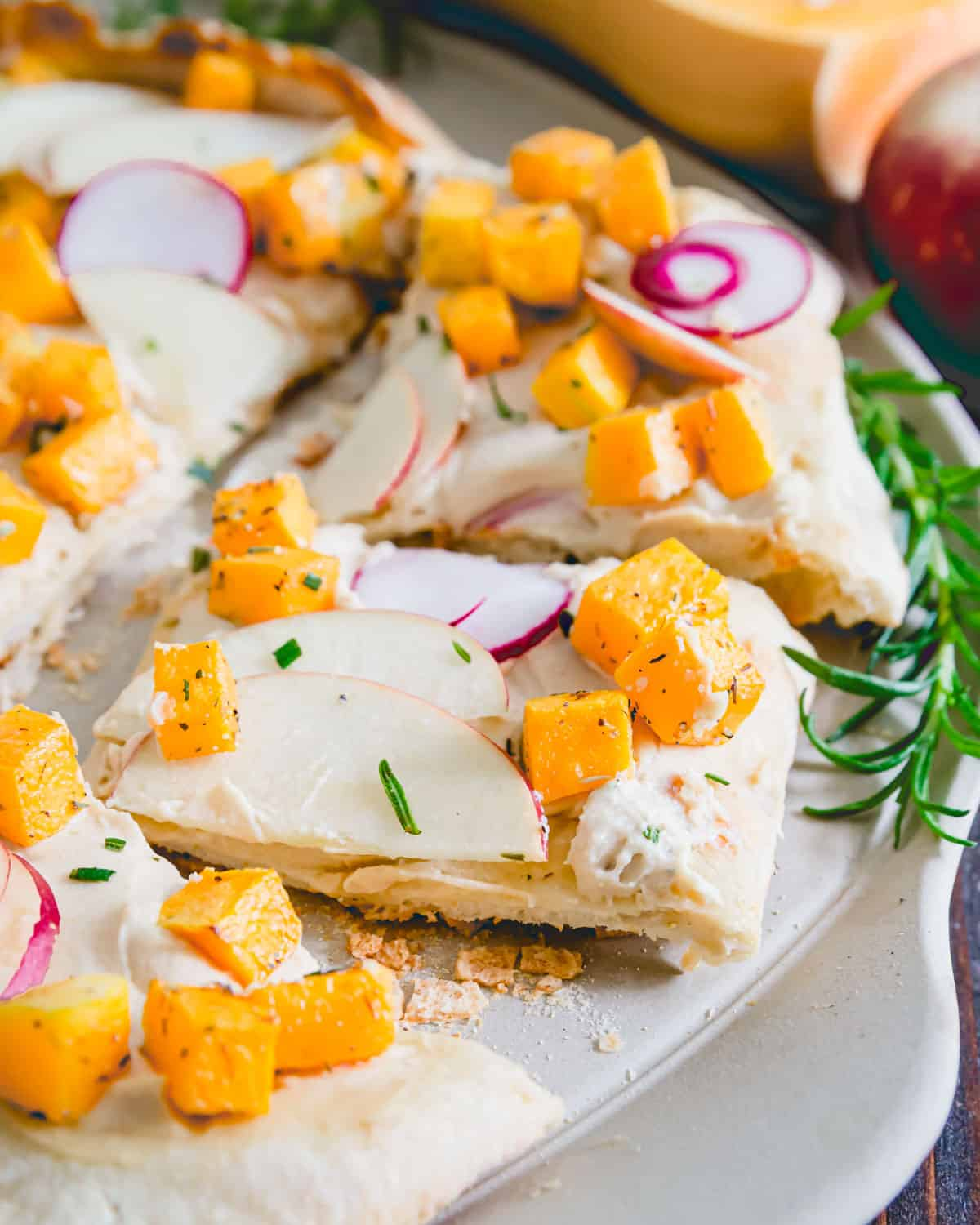 Hummus replaces cheese on this non-traditional fall inspired pizza with rosemary roasted butternut squash, apples and radishes.