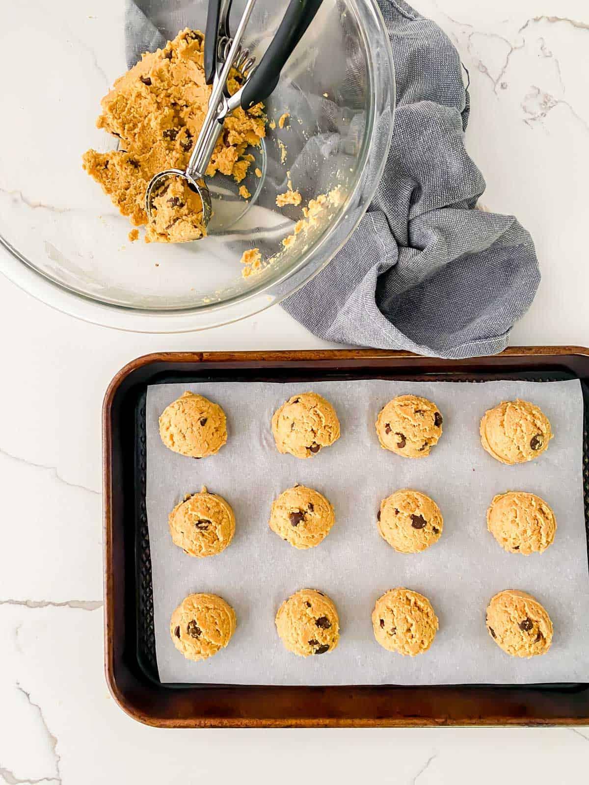 using a cookie dough scoop to shape pumpkin cookie dough into balls