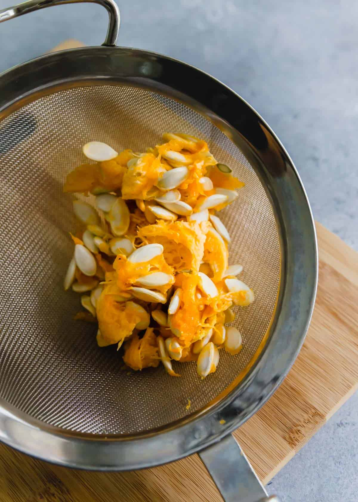 squash seeds before cleaning with pulp still attached in a colander.
