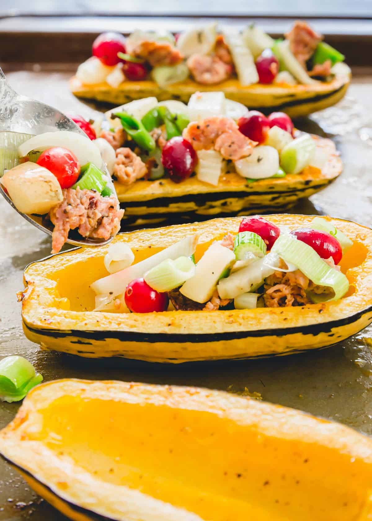 """Stuffing the roasted delicata squash """"boats"""" with the ground pork filling."""
